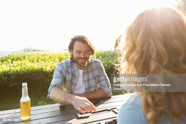 Couple playing dominoes at campsite picnic table