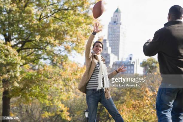 couple playing football in park - homem pegando mulher imagens e fotografias de stock