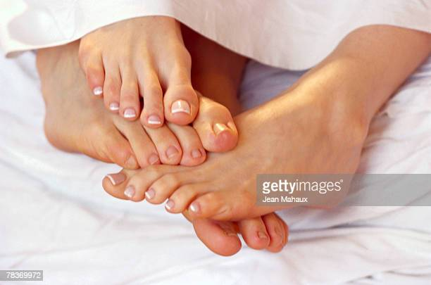 couple playing footsie - barefoot footsie stock photos and pictures