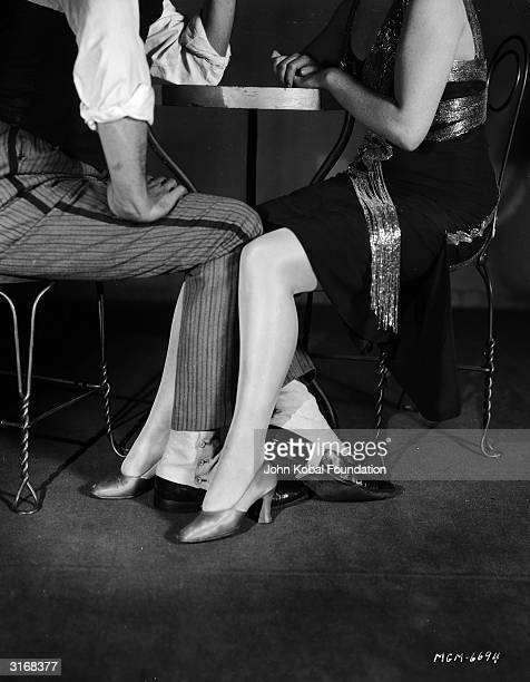 A couple playing footsie under a table in the film 'Adam Had Four Sons' which established Ingrid Bergman as an American star A Columbia production...
