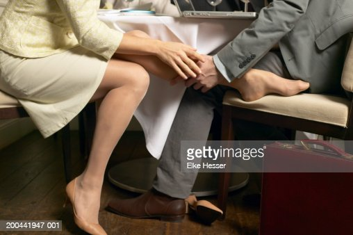 Couple Playing Footsie Under Restaurant Table Stock Photo