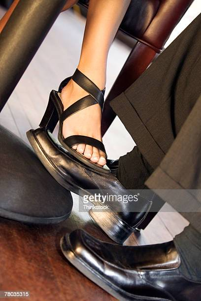 couple playing footsie under table - playing footsie stock photos and pictures