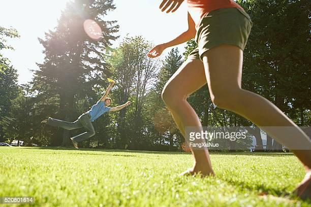 couple playing frisbee - homem pegando mulher imagens e fotografias de stock
