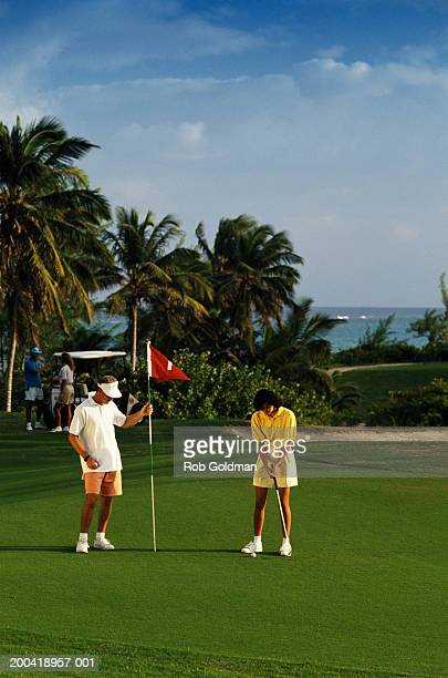 Couple playing golf, sea in background
