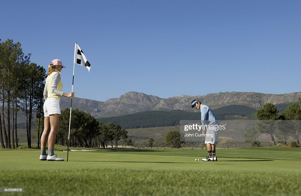 Couple Playing Golf, Woman Holding up a Flag : Stock Photo