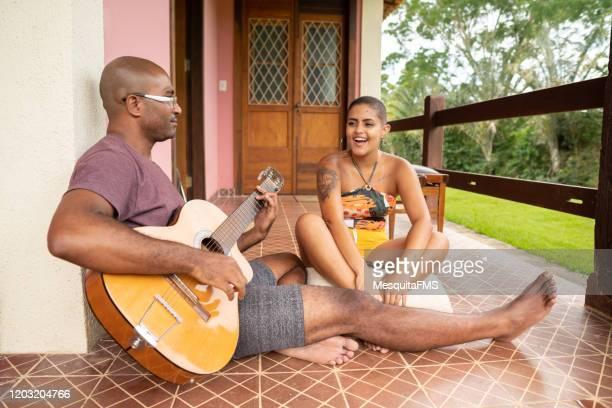 couple playing guitar on home porch - sentar se imagens e fotografias de stock