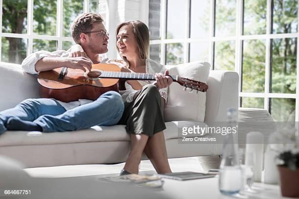 Couple playing guitar on sofa