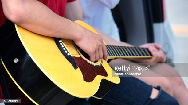 Couple playing guitar on the back of a family car on holiday.