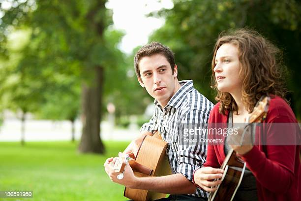 couple playing guitars in park - peterborough ontario stock photos and pictures