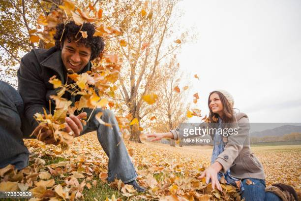 Couple playing in autumn leaves