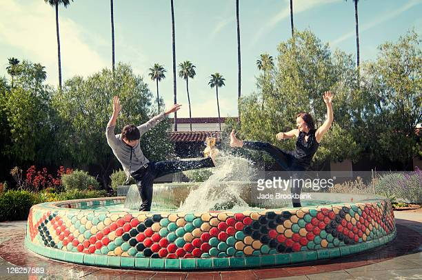 Couple playing in water fountain