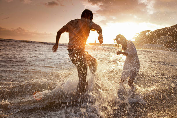 Couple Playing In Waves At Beach Wall Art