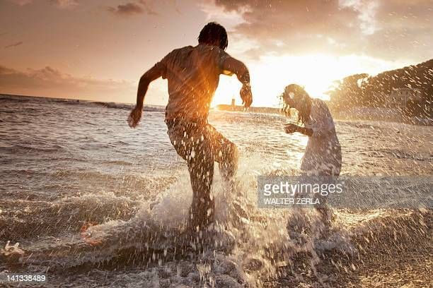 Couple playing in waves at beach