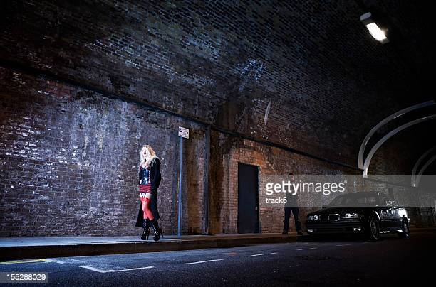 couple playing master and servant in a dark highway tunnel. - prostitutie stockfoto's en -beelden