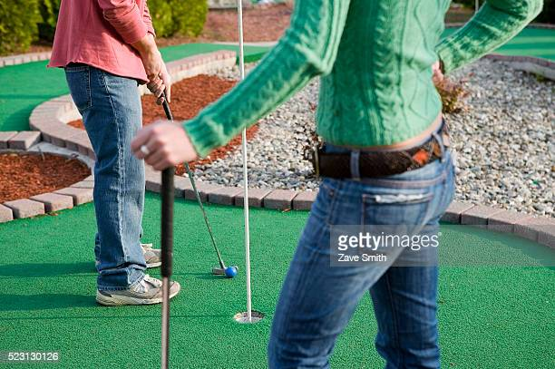 Couple Playing Miniature Golf