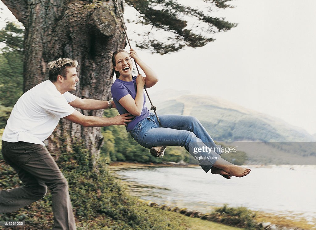 Couple Playing on a Rope Swing, Man Pulling Woman : Stock Photo
