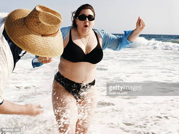 Couple playing on beach, man splashing woman with water
