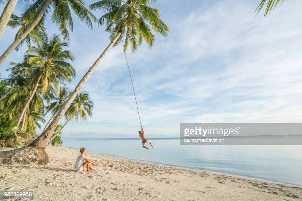 couple playing on beach, swing rope on palm tree in tropical island asia - honeymoon stock pictures, royalty-free photos & images