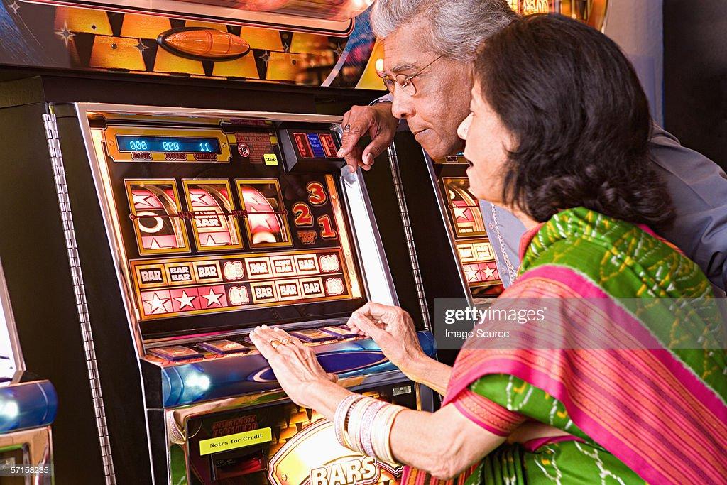 Couple playing on fruit machine : Stock Photo