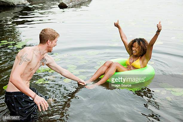 Couple playing on inflatable ring on lake