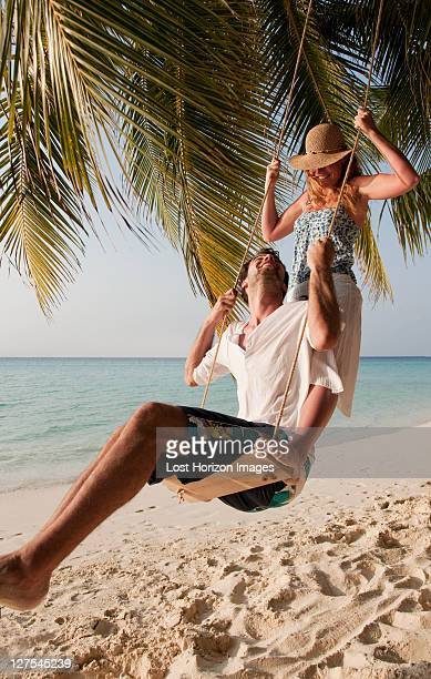 couple playing on swing at beach - indian ocean stock pictures, royalty-free photos & images