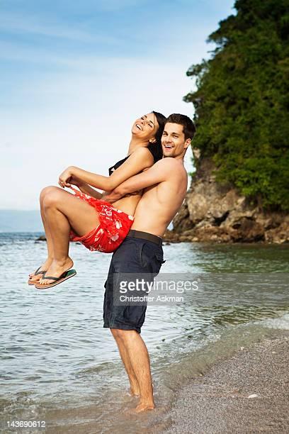 Coppia gioca sulla spiaggia tropicale