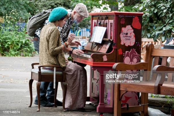 Couple playing one of 30 pianos placed around London, England, for three weeks as a public art project on 25th June 2009.