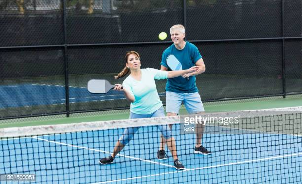 couple playing pickleball, hispanic woman hitting ball - doubles stock pictures, royalty-free photos & images