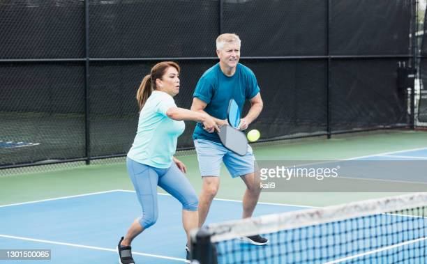 couple playing pickleball, woman hitting ball - doubles stock pictures, royalty-free photos & images