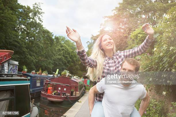 Couple playing piggyback by canal, East London, UK