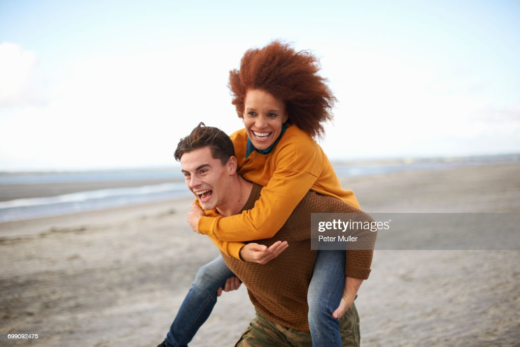 Couple playing piggyback on beach : Stock Photo