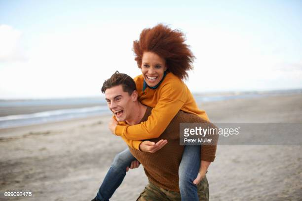 couple playing piggyback on beach - mixed race person stock pictures, royalty-free photos & images