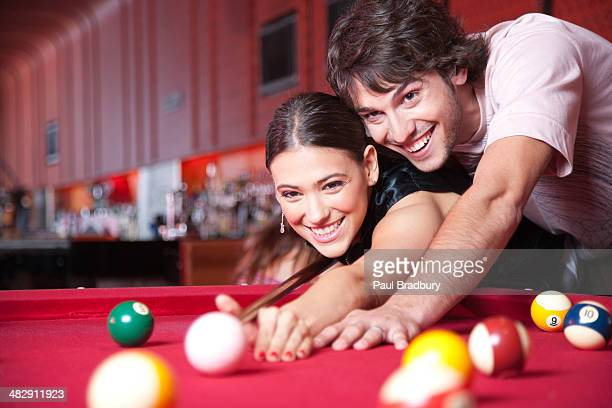 Couple playing pool and smiling