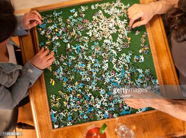 couple playing puzzle - puzzle stock pictures, royalty-free photos & images