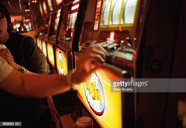 couple playing slot machine in casino, las vegas, nevada, usa - slot machine stock pictures, royalty-free photos & images