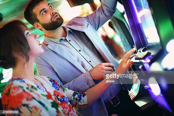 Couple playing slots in casino.