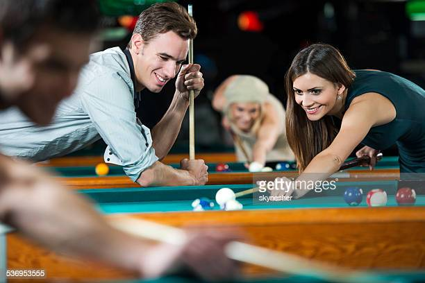 Couple playing snooker.