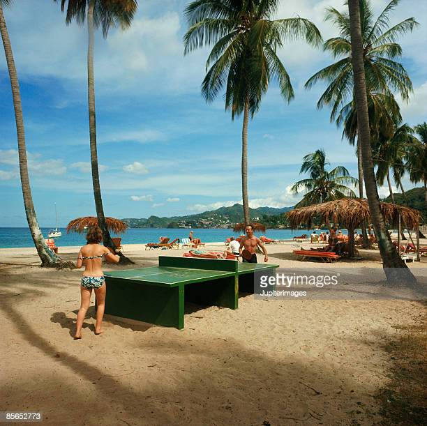 Couple playing table tennis on beach