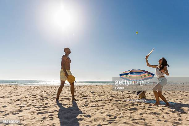 Couple playing tennis at beach against clear sky