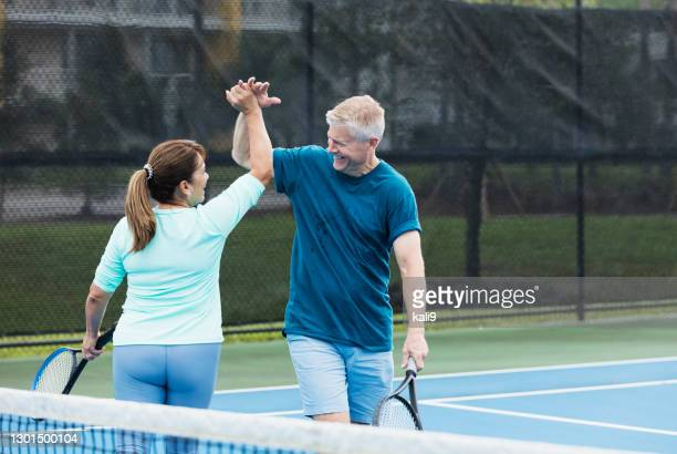 couple playing tennis, high fives for winning shot - doubles stock pictures, royalty-free photos & images