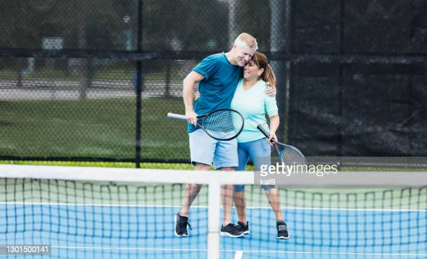 couple playing tennis, hugging - doubles stock pictures, royalty-free photos & images