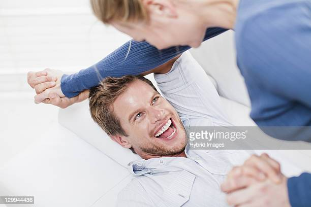 couple playing together on couch - rough housing stock photos and pictures