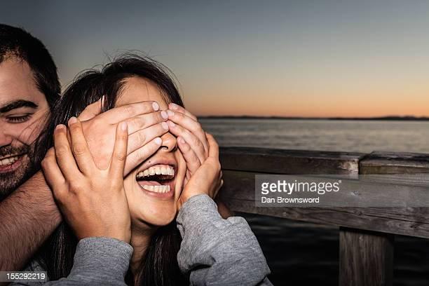 couple playing together outdoors - augen zuhalten stock-fotos und bilder