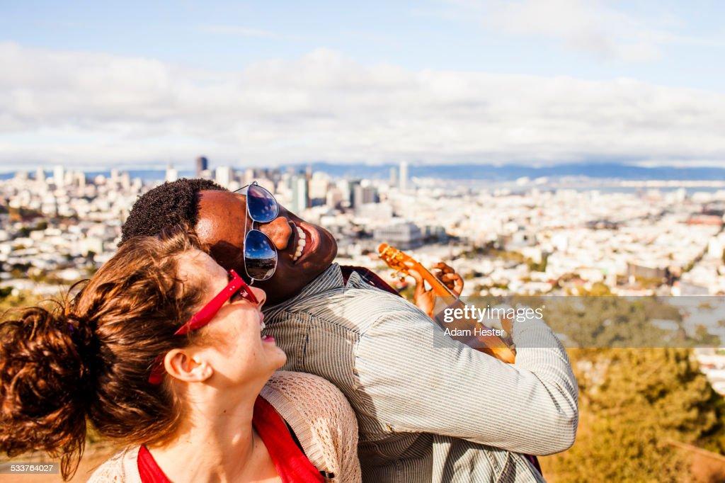 Couple playing ukulele near scenic view of cityscape : Foto stock