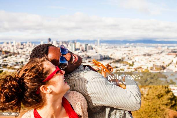 couple playing ukulele near scenic view of cityscape - multikulturalismus stock-fotos und bilder