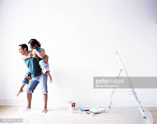 Couple playing while painting room