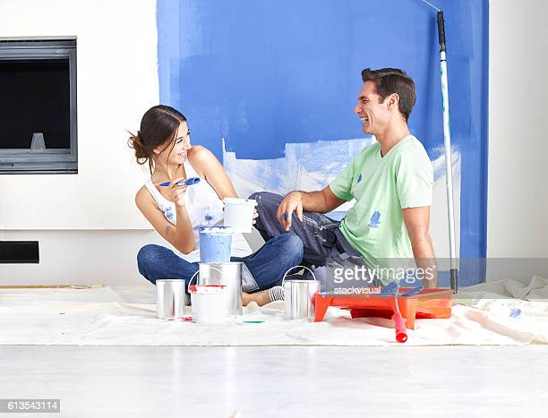 Couple playing while painting the wall