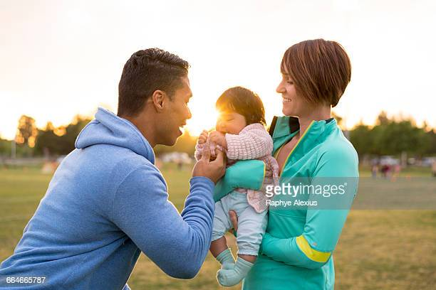 couple playing with baby in park - white wife black baby stock photos and pictures