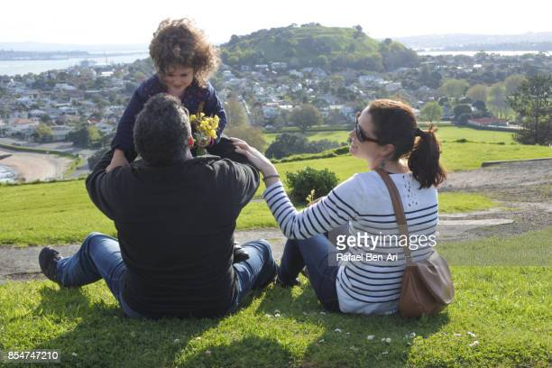 couple playing with daughter outdoors - rafael ben ari stockfoto's en -beelden