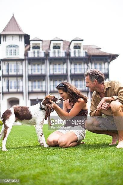 Couple playing with dog in village park